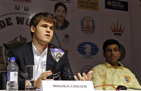 Norway's Magnus Carlsen speaks during a news conference as India's Viswanathan Anand (R) looks on after Carlsen clinched the FIDE World Ches