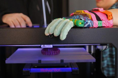 Twelve-year-old Leon McCarthy rests his prosthetic hand on a MarkerBot Replicator 2 Desktop 3D Printer at the new MakerBot store in Boston,