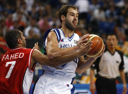 Greece's Vassilis Spanoulis (R) is challenged by Lebanon's Rony Fahed during their basketball game at FIBA Olympic qualifying tournament in