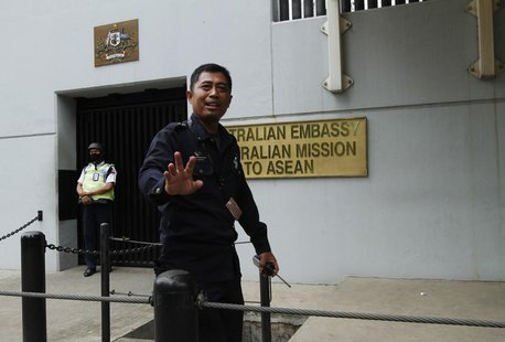 A security personnel raises his hand in an attempt to stop the media from taking pictures in front of the Australian Embassy gate in Jakarta