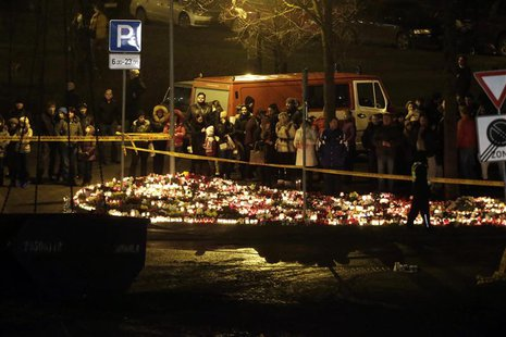People gather near lit candles in front of a collapsed supermarket in capital Riga November 23, 2013. REUTERS/Ints Kalnins
