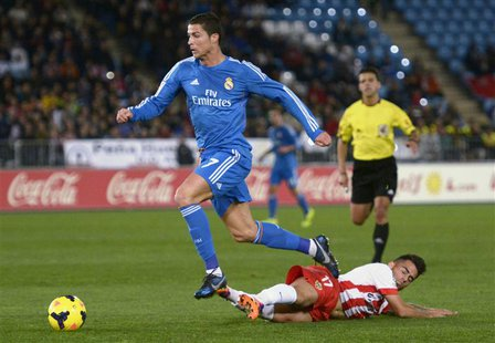 "Real Madrid's Cristiano Ronaldo (top) is challenged by Almeria's Jesus Joaquin Fernandez ""Suso"" during their Spanish First Division soccer m"