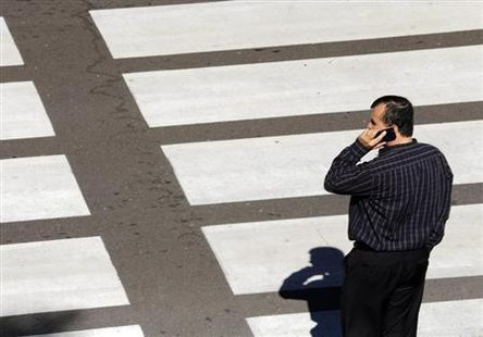 A man talks on his mobile phone as he waits at a crosswalk at Lindbergh Field Airport in San Diego, California, November 6, 2013.  Credit: Reuters/Mike Blake