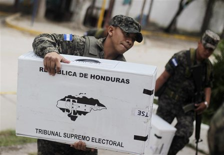 Soldiers carry ballot boxes into a school to be converted into a polling station in Tegucigalpa November 23, 2013. REUTERS/Jorge Cabrera