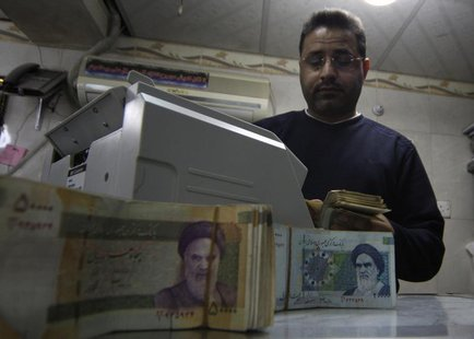 A man counts stacks of Iranian rials at a currency exchange shop in Kerbala , 110 km (70 miles) south of Baghdad January 23, 2013. REUTERS/M