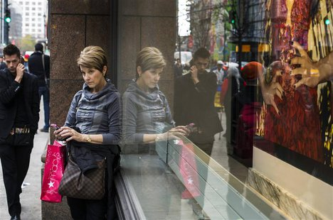 A woman stops to use her phone in front of holiday window displays at Macy's flagship store in New York, November 22, 2013. REUTERS/Lucas Ja