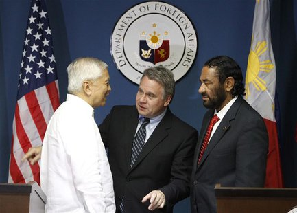 Philippine Foreign Affairs Secretary Albert Del Rosario (L) chats with U.S. Representatives Chris Smith and Al Green (R) after their news co