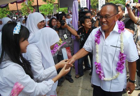 Indonesian billionaire businessman and chairman of Golkar Aburizal Bakrie (R) greets school students during a roadshow in Tangerang outskirt