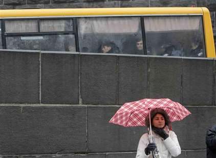 Police are seen in a bus while a protester stands with her umbrella during a rally in support of EU integration in front of the Ukrainian ca