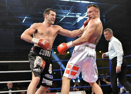 Carl Froch (L) of Britain punches Mikkel Kessler of Denmark during their super-middle weight title bout in Herning April 24, 2010. REUTERS/S