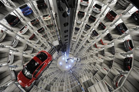 "A Volkswagen ""Beetle"" (L) and an ""UP!"" are pictured in a delivery tower at the company's headquarter in Wolfsburg, March 12, 2012. REUTERS/F"