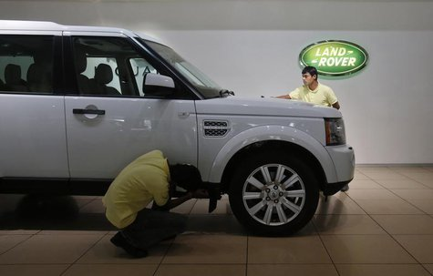 Showroom attendants polish a Land Rover vehicle at a Jaguar Land Rover showroom in Mumbai February 13, 2013. REUTERS/Vivek Prakash
