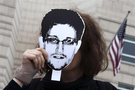 A woman holds a portrait of former U.S. spy agency contractor Edward Snowden in front of her face as she stands in front of the U.S. embassy