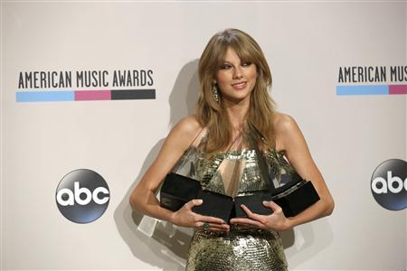 Musician Taylor Swift poses backstage with her awards for artist of the year, favorite country artist - female, favorite country album for ''Red'' and favorite female pop/rock at the 41st American Music Awards in Los Angeles, California November 24, 2013. CREDIT: REUTERS/MARIO ANZUONI