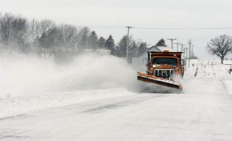 A snowplow clears a road from a past storm