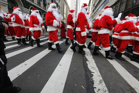 Santas cross the street while marching through Midtown Manhattan during the Volunteers of America's 110th Annual Sidewalk Santa Parade in Ne