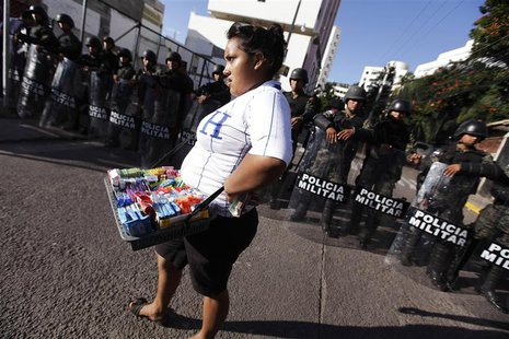 A street vendor walks past a police blockade during a protest by supporters of presidential candidate Xiomara Castro in Tegucigalpa November