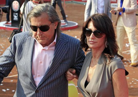 Gymnast Nadia Comaneci (R) and former tennis player Ilie Nastase of Romania leave the court after the awards ceremony at the Bucharest Inter
