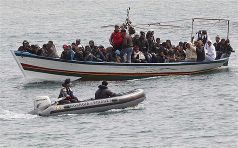 Migrants from North Africa arrive, escorted by Italian Guardia di Finanza, at the southern Italian island of Lampedusa in this March 14, 201