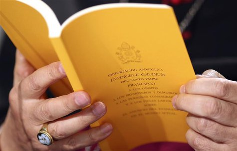 The document of the Evangelii Gaudium (The Joy of the Gospel) from Pope Francis is seen as Bishop Carlo Maria Celli reads during a presentat