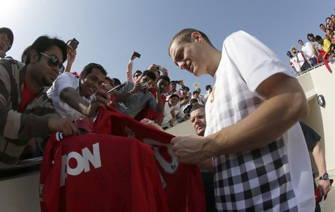 Manchester United's Nemanja Vidic signs autographs for fans before a training session at the Aspire Academy for Sports Excellence in Doha Ja