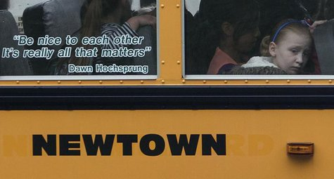 Students sit behind a quote by slain Sandy Hook Elementary School principal Dawn Hochsprung, displayed on the window of a school bus, as it