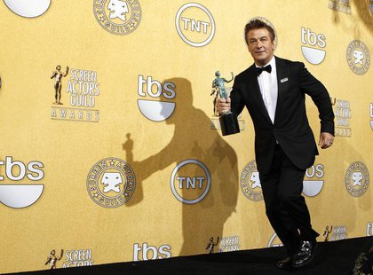 "Actor Alec Baldwin runs backstage with his award for outstanding performance by a male actor in a comedy series for ""30 Rock"", at the 18th a"