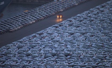 A truck is driven down a road at a yard where cars are parked before being exported at a port in Incheon, west of Seoul June 17, 2012. REUTE