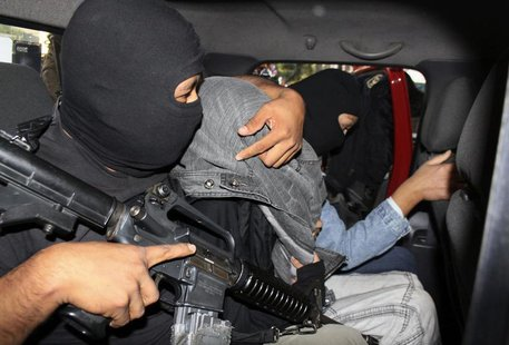 "A police officer drapes a jacket over the head of a suspect believed to be Edgar Jimenez (C), also known as ""El Ponchis"", after escorting hi"