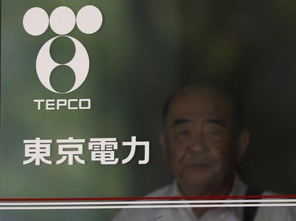 A man walking out is seen past Tokyo Electric Power Co (TEPCO)'s logo at the company headquarters in Tokyo July 19, 2012. REUTERS/Yuriko Nak