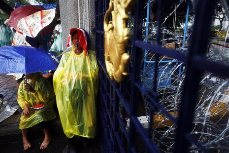Anti-government protesters protect themselves from the rain as they stay at the gates of the Interior Ministry in Bangkok November 26, 2013.
