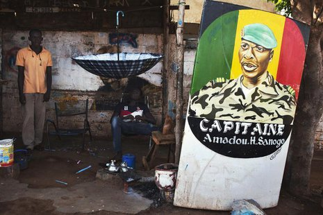 Men sit next to a painting of the ex-junta leader Amadou Haya Sanogo in Bamako July 16, 2013. Mali will be holding presidential election on