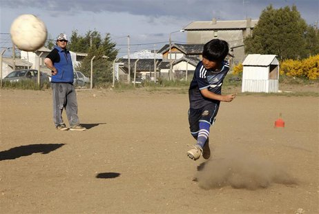 Claudio Nancufil (R) kicks the ball at the Club Martin Guemes in the Patagonian Argentine city of Bariloche November 26, 2013. REUTERS/Chiwi
