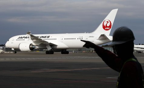 A staff of Japan Airlines' (JAL) walks past one of the company's Boeing Co's 787 Dreamliner plane at Narita international airport in Narita,