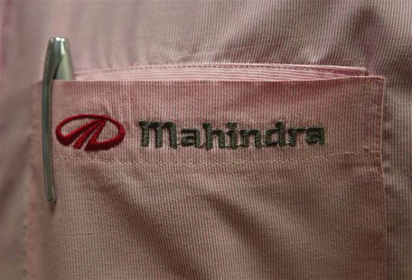 The logo of Mahindra & Mahindra Ltd is pictured on the pocket of a salesman's shirt as he poses inside the company's showroom in Mumbai, in