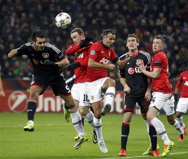 Bayer Leverkusen's Emir Spahic (L) is challenged by Manchester United's Wayne Rooney (2nd L) and Ryan Giggs (3rd L) during their Champions L