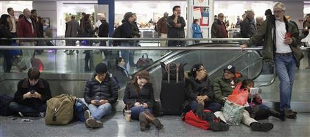 . Travelers sit and wait at Penn Station in New York, November 26, 2013.  CREDIT: REUTERS/CARLO ALLEGRI