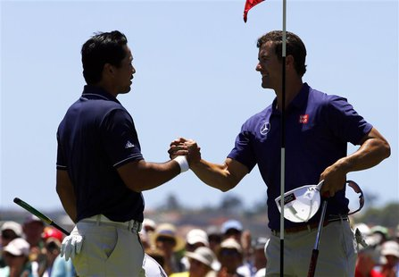 Australia's Adam Scott (R) shakes hands with playing partner and fellow countryman Jason Day after they finished their first rounds of the A