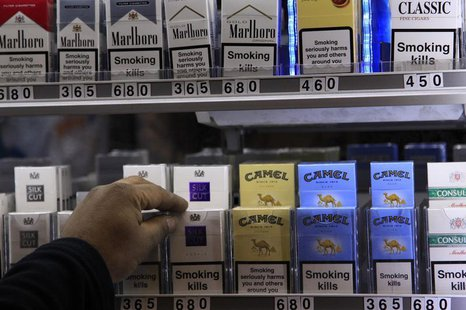 A shopkeeper reaches for a packet of cigarettes in a newsagent in London March 9, 2011. REUTERS/Stefan Wermuth