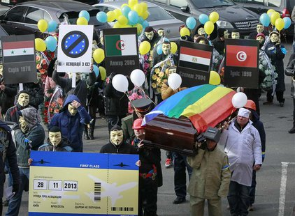 People dressed in outfits of various popular professions in Ukraine carry a coffin symbolising Ukraine's Euro-association and an airplane ti