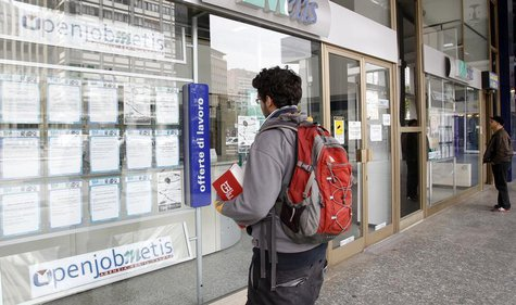 A man checks job offers outside a recruitment agency in downtown Milan April 3, 2012. REUTERS/Alessandro Garofalo