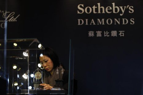 A member of staff checks a display prior to the exhibition sale of Sotheby's Diamonds during Sotheby's Beijing Art Week in Beijing, November