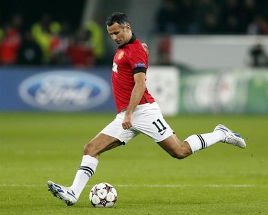 Manchester United's Ryan Giggs kicks the ball during the Champions League Group A soccer match against Bayer Leverkusen at the BayArena in L
