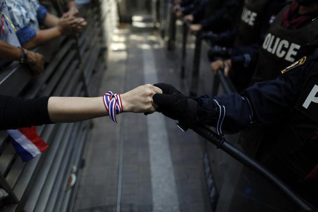 An anti-government protester holds hands with an anti-riot policemen across the closed gates outside the headquarters of the ruling Puea Tha
