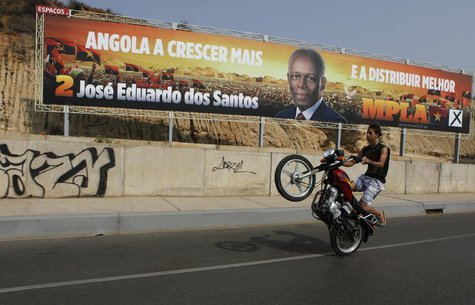 A motorcyclist rides past an election poster of the ruling MPLA party with the picture of President Jose Eduardo dos Santos in the capital L