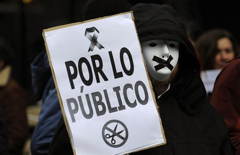 A protestor wears a mask with black tape over the mouth during a demonstration against government austerity measures and the passing of a ne