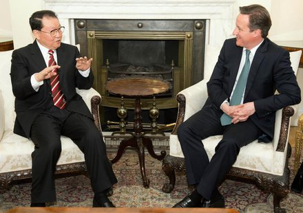 Li Changchun, a member of China's Standing Committee of the Political Bureau (L) speaks to Britain's Prime Minister David Cameron during the
