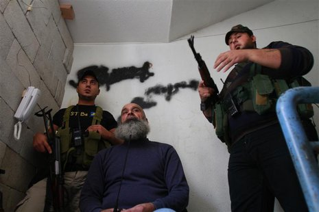 Sunni Muslim fighters stand with their weapons inside a building in Tripoli, northern Lebanon, November 30, 2013. REUTERS/Omar Ibrahim