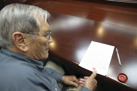 U.S. citizen Merrill E. Newman puts his thumbprint on a piece of paper, after being taken into custody by North Korea, after entering North