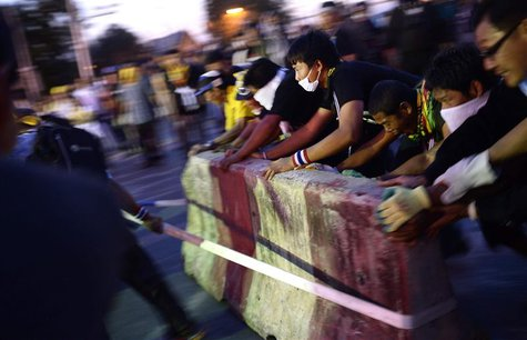 Anti-government protesters tear down barricades during a demonstration outside Government House in Bangkok November 30, 2013. REUTERS/Dylan